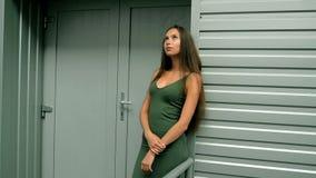 La belle fille dans la robe verte se tient près d'un mur en métal banque de vidéos