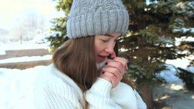 La belle fille dans un chapeau et un chandail chauffe ses mains respirant sur elles banque de vidéos