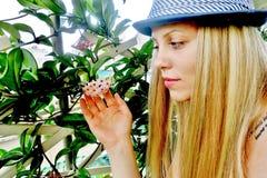 La belle fille dans un chapeau regarde une fleur image stock