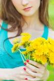 La belle fille dans un jour d'été ensoleillé marchant dans le jardin et maintient les pissenlits jaunes dans les mains Photo libre de droits