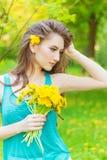 La belle fille dans un jour d'été ensoleillé marchant dans le jardin et maintient les pissenlits jaunes dans les mains Photos libres de droits