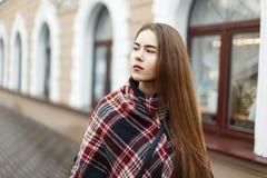 La belle fille dans un vintage a barré l'écharpe sur la rue photo libre de droits
