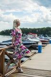 La belle fille dans une robe est position sur le pilier contre le contexte des yachts en été images stock