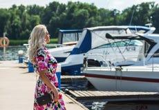 La belle fille dans une robe est position sur le pilier contre le contexte des yachts en été image stock