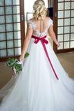 La belle fille dans une robe l'épousant se tient au milieu de la salle avec le sien de nouveau à la caméra photo stock