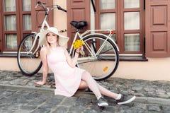 La belle fille dans une robe rose s'assied près d'une bicyclette sur une vieille route, utilisant un chapeau avec des fleurs dans photo libre de droits