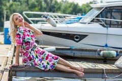 La belle fille dans une robe s'assied sur le pilier contre le contexte des yachts en été photo libre de droits
