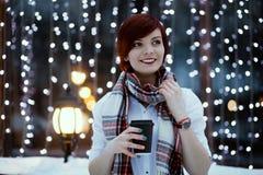 La belle fille dans la ville sur un fond de la soirée allume tenir le café Photographie stock