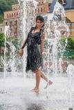La belle fille danse dans une fontaine images stock