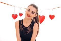 La belle fille de brune dans la robe noire avec gentil composent pour célébrer le jour de valentines avec le coeur rouge dans le  Images stock