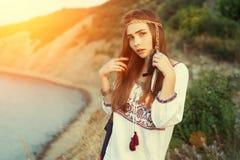 La belle fille de brune dans le style chic de Bocho se tient sur le fond de la mer dans les rayons d'un soleil lumineux Ton de co Image libre de droits