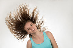 La belle fille de brune fait une oscillation avec les cheveux bouclés sur un blanc Photos libres de droits