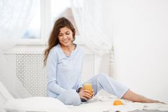 La belle fille de brune habillée dans le pyjama bleu-clair s'assied sur le lit avec le verre de jus frais dans la lumière confort images libres de droits