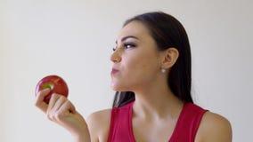 La belle fille de brune mange Apple rouge sur un blanc banque de vidéos