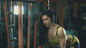 La belle fille de brune s'exerce avec le cadre de bloc dans le gymnase foncé banque de vidéos
