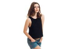 La belle fille de goupille- regarde dans l'appareil-photo et maintient ses mains dans ses poches dans des shorts de denim photos stock