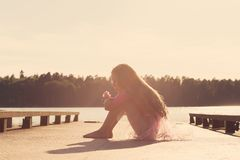 La belle fille de l'adolescence triste s'assied avec le visage sérieux au bord de la mer Images libres de droits
