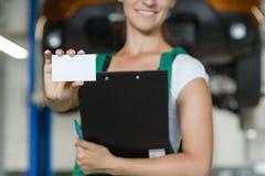 La belle fille de mécanicien montre sa carte de visite professionnelle de visite images libres de droits