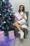 La belle fille de sourire aux cheveux longs dans un chandail blanc sexy s'assied sur une chaise grise à côté de l'arbre de Noël B photos libres de droits