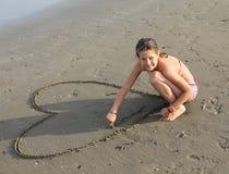 La belle fille de sourire dessine beaucoup de coeurs sur la plage Image stock