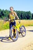 La belle fille de sourire marche avec la bicyclette Photographie stock libre de droits