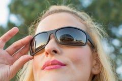 la belle fille de sourire utilise des lunettes de soleil Photographie stock libre de droits