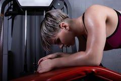 La belle fille de sport est engagée sur un simulateur dans le gymnase Sportive en sueur après séance d'entraînement intense de fo photographie stock libre de droits