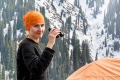 La belle fille de touristes avec des jumelles se tient près d'une tente dans la perspective des montagnes couronnées de neige Images stock