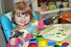 La belle fille dessine avec des peintures de doigt Image stock