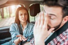 La belle fille discute avec son ami Elle n'est pas satisfaisante Le type couvre son visage de main il est très fatigué Photos libres de droits