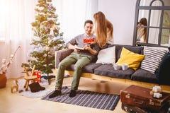 La belle fille donne à son ami un arbre de Noël proche actuel Photographie stock libre de droits