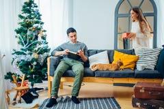 La belle fille donne à son ami un arbre de Noël proche actuel Images libres de droits