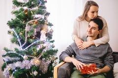 La belle fille donne à son ami un arbre de Noël proche actuel Photo stock