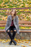 La belle fille douce avec les grands yeux tristes dans le manteau se reposant sur le banc en automne parmi le jaune tombé laisse  images libres de droits