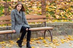 La belle fille douce avec les grands yeux tristes dans le manteau se reposant sur le banc en automne parmi le jaune tombé laisse  image libre de droits