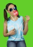 La belle fille drôle utilisant des lunettes de soleil avec la bulle du chewing-gum écoute la musique image libre de droits