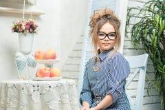 La belle fille en verres s'assied à une table avec le fruit dans une salle lumineuse Images stock