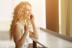 La belle fille est heureuse au téléphone, elle a été faite à une bonne offre photographie stock