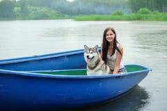 La belle fille et un chien enroué dans le bateau photos stock