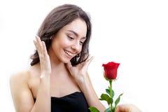 La belle fille fâchée reçoit une rose de rouge Elle est étonnée, regardant les fleurs et le sourire Images stock
