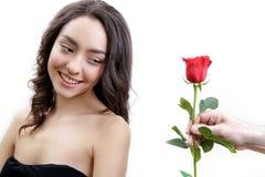 La belle fille fâchée reçoit une rose de rouge Elle est étonnée, regardant les fleurs et le sourire Photos libres de droits