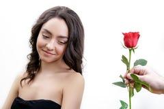 La belle fille fâchée reçoit une rose de rouge Elle est étonnée, regardant les fleurs et le sourire de débuts Photo stock