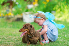 La belle fille féerique joue avec un chien sur l'herbe Photographie stock libre de droits