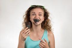 La belle fille gaie avec les cheveux bouclés mange la crème glacée noir dedans Image stock
