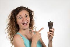 La belle fille gaie avec les cheveux bouclés mange la crème glacée noir dedans Photos libres de droits