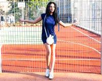 La belle fille grande de brune dans une robe bleue courte et avec un sac à main marche en parc de sports Photos libres de droits