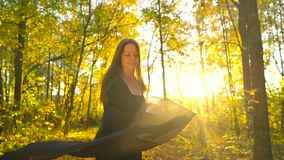 La belle fille habillée dans la robe noire marche dans la forêt d'automne et apprécie le temps beau banque de vidéos