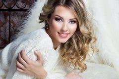 La belle fille heureuse de sourire avec le maquillage lumineux se trouve sur le lit avec la fourrure dans le chandail blanc Photographie stock libre de droits