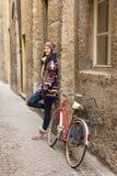 La belle fille heureuse se tient à côté d'une bicyclette dans le petit stre Photos stock