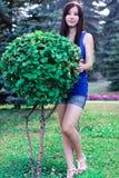 La belle fille intégrale en parc près des buissons décoratifs Images stock